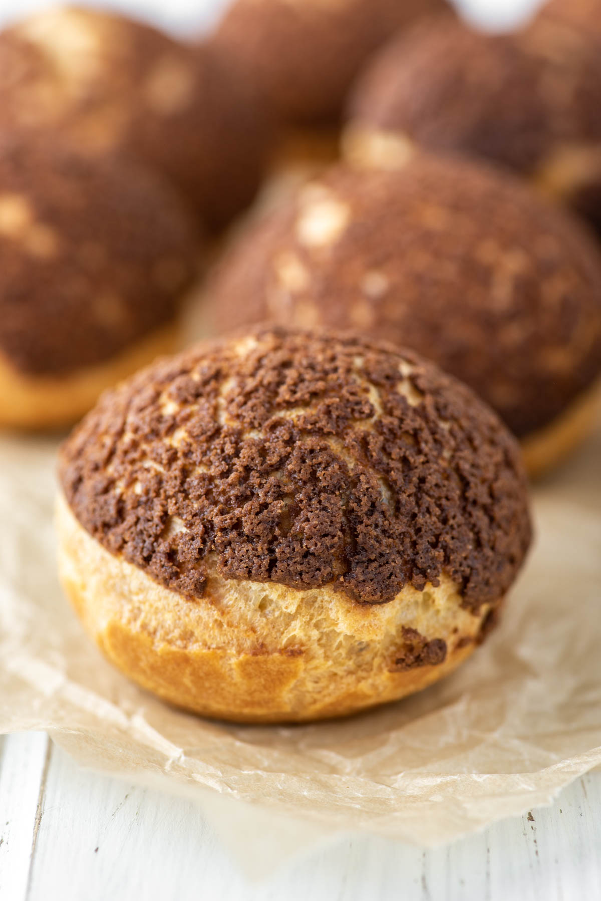 chocolate cream puff on parchment paper with more in background