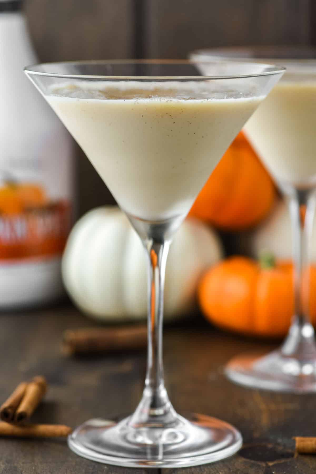 two glasses of pumpkin martini with pumpkins in the background
