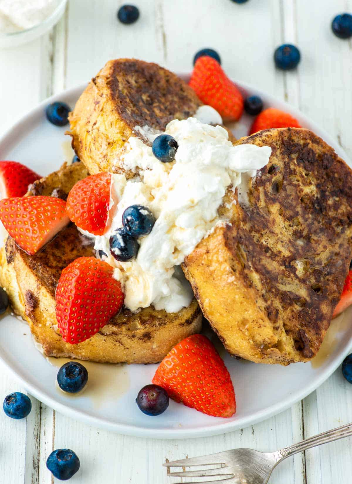 3 stacked slices of French toast on plate with whipped cream and fruit