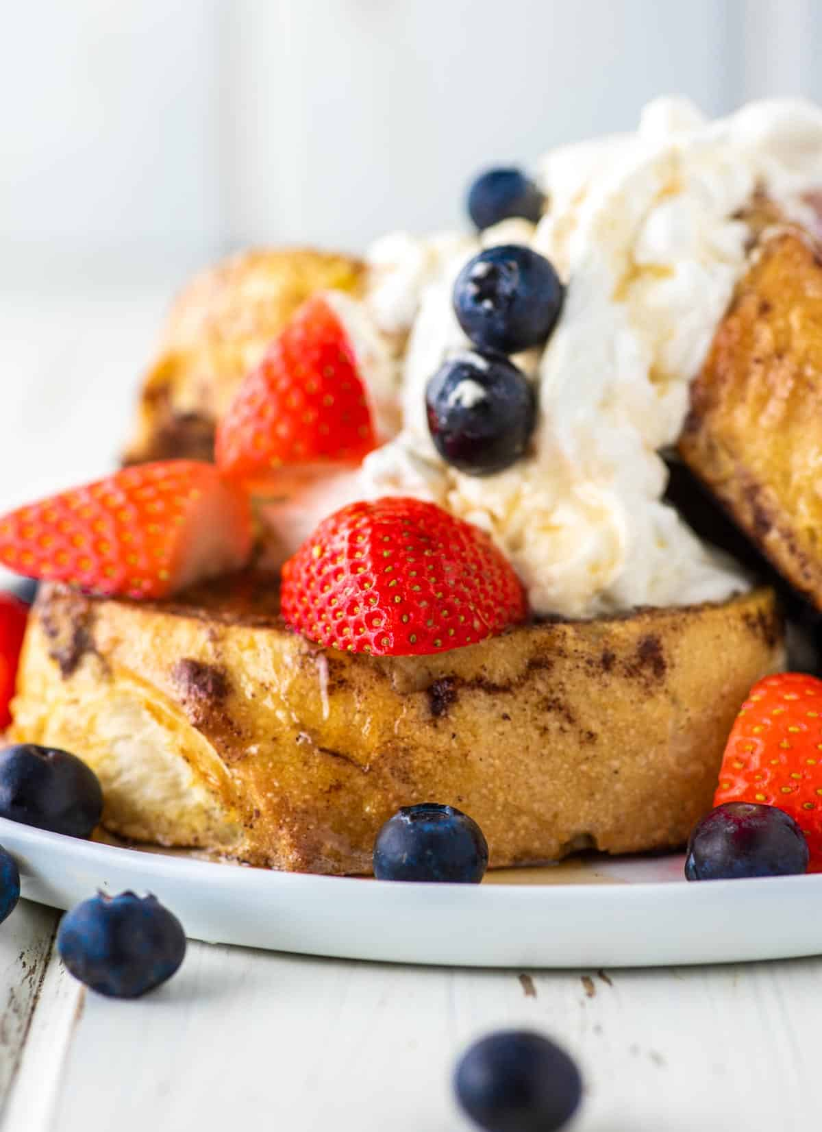 sourdough French toast stacked on white plate with whipped cream and fruit