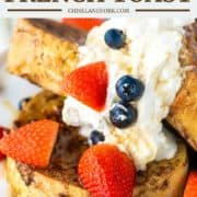 3 slices of sourdough French toast on white plate with whipped cream, strawberries and blueberries
