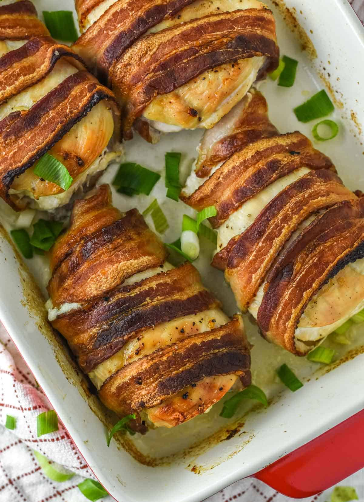 overhead shot of chicken wrapped in bacon in baking dish