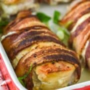 bacon wrapped stuffed chicken in red baking dish