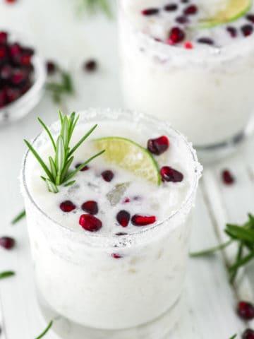 two glasses of White Christmas Margaritas on white board