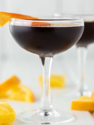 Black Manhattan with orange peel in coupe glass