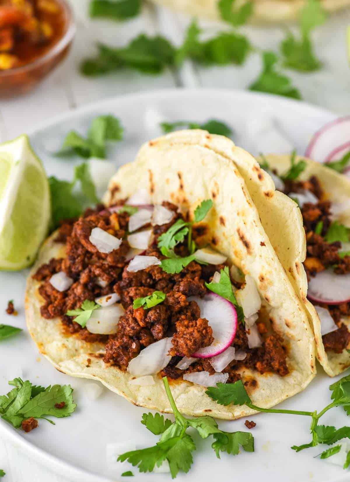 two chorizo tacos on white plate