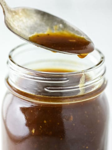 spoon dipped in mason jar with balsamic dressing