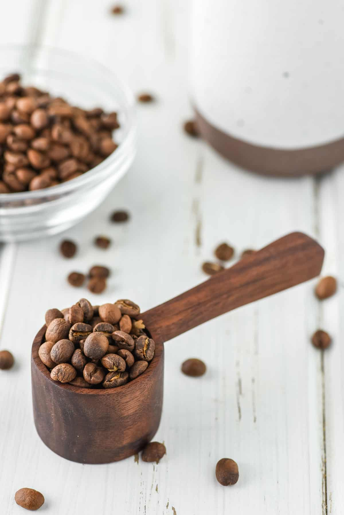 wooden coffee scoop with coffee beans on white board and coffee mug in background