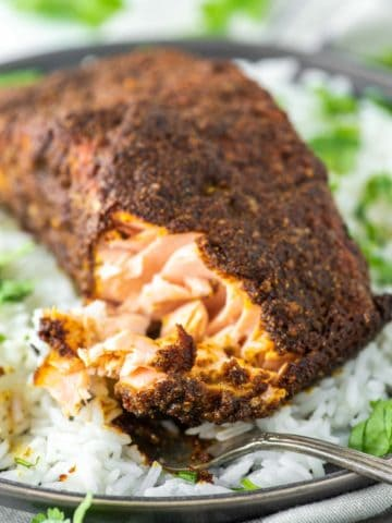 fork cut into tandoori salmon on plate of white rice