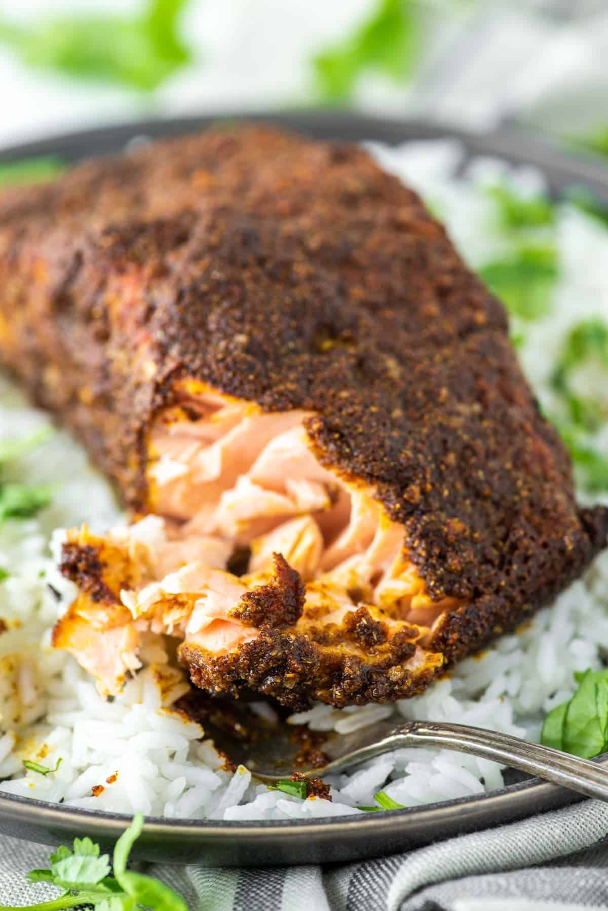 fork cut into tandoori salmon on plate of white rice