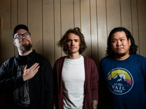 Band members standing in front of wood paneled wall