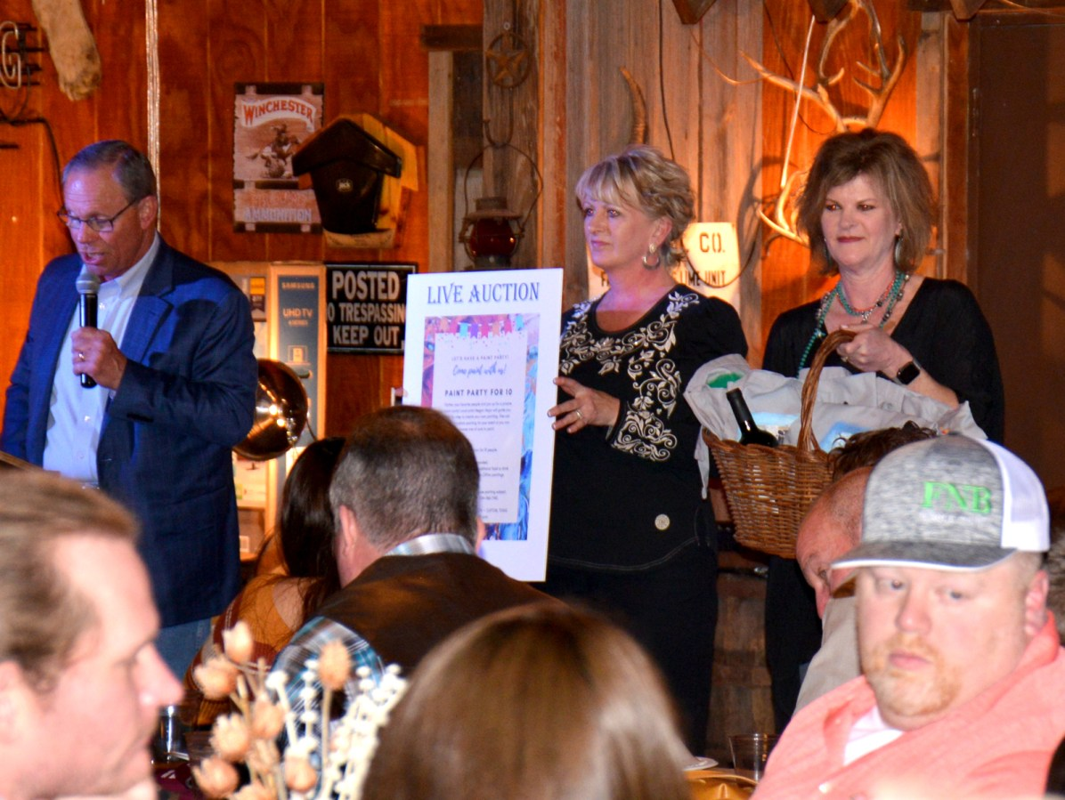 Tom Henderson assisted by Paige Key and Lisa Horn during the live auction.
