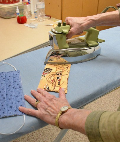 Award-winning Bosque Arts Center Quilt Guild member Sidney Carlisle ironing face masks for the Goodall-Witcher healthcare facility.