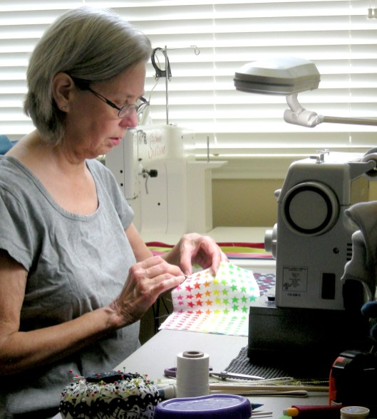 Bosque Arts Center Quilt Guild President Linda Pfeiffer sewing face masks for the Goodall-Witcher healthcare facility.
