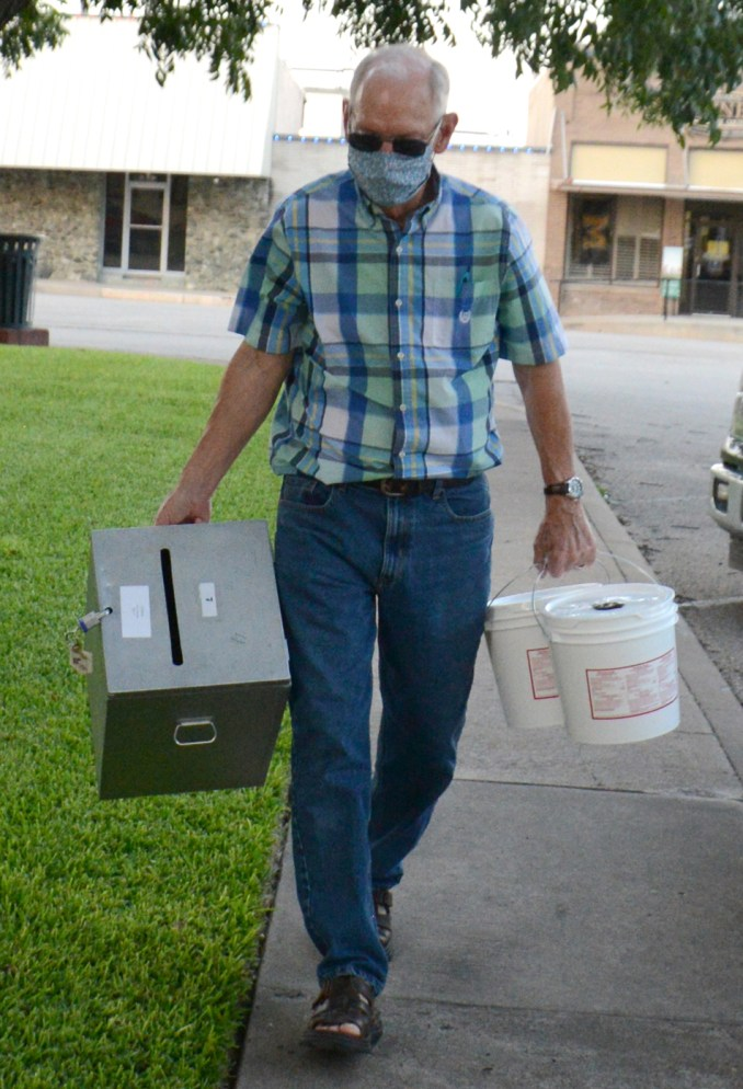 Election judges carry in election materials during the Runoff Election July 14 between Republican candidates for Bosque County Sheriff Clint Pullin and Trace Hendricks.