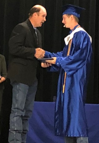 Clint Pullin presents his son Matthew with his diploma.
