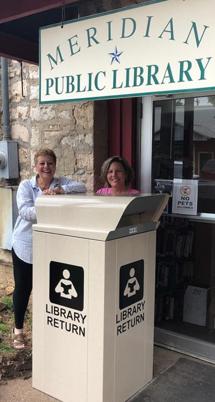 Meridian Public Library Director Marianne Woerner and Board President Pam Hardcastle show off the new return box behind the library. The box was received through a grant.