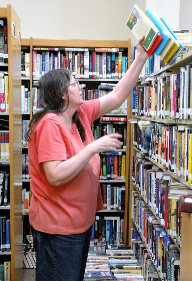 The late Lesli Scott, Longtime Meridian Public Library Librarian, organizes books into new shelves, purchased through a Tocker Foundation Grant.