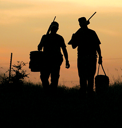 Father and son hunters pack it in at end of day with sunset