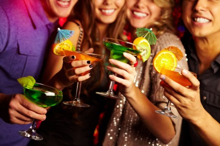 Young people having fun at a party with cocktails