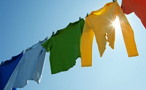 Multicolored clothing will be dried on the street on the rope