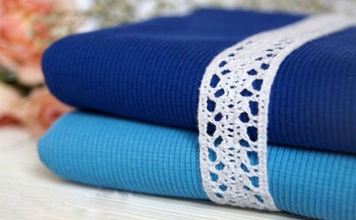 Roll of blue and blue fabric lie on the table