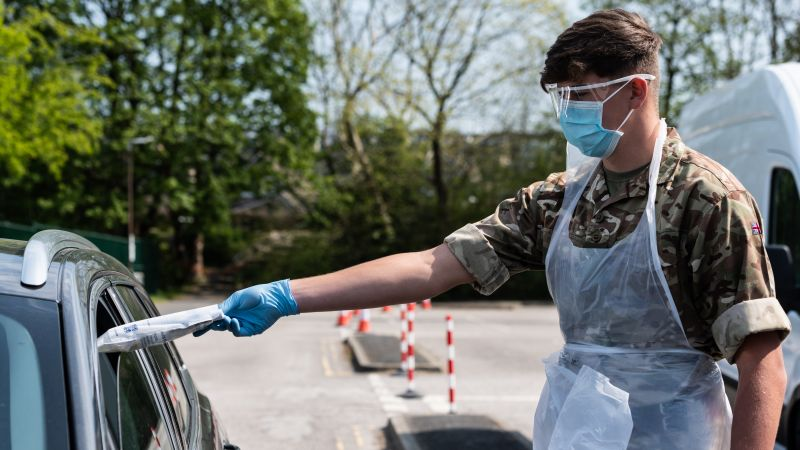 Soldier posts COVID19 coronavirus testing kit through the car window at the Mobile Testing Unit i