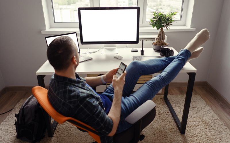 Man relaxing while working remotely from home holding legs on the table looking at the computer holding phone with window in background