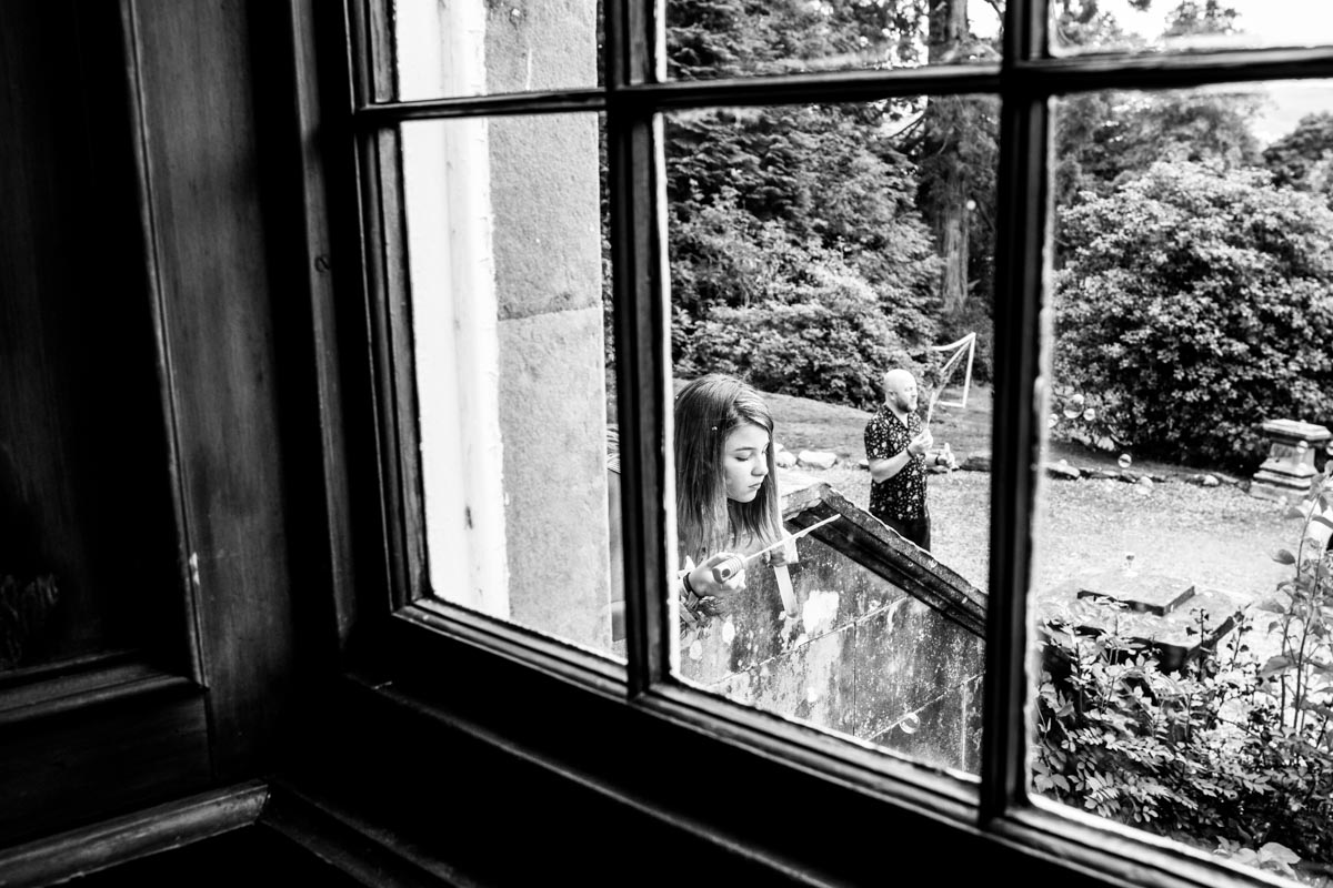 A girl blowing bubbles on the other side of the window. Edinburgh wedding photographer. Glasgow wedding photography.