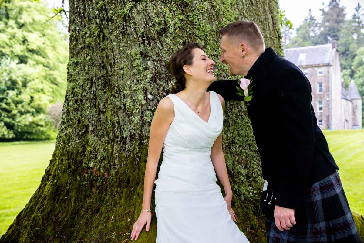 Bride and groom leaning against tree at Culcreuch Castle