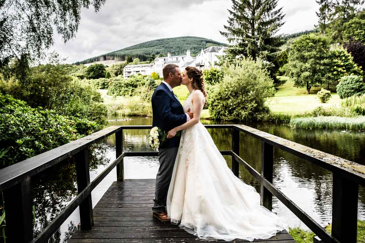 Bride and groom kissing at the lake MacDonald Forest Hills Hotel