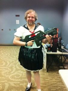 Shokolada wearing a black-and-white PVC schoolgirl fuku, carrying an Aliens pulse rifle prop.