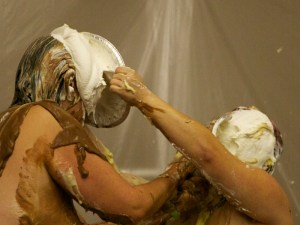 Mistress Messiér and Maya Kralovna exchange simultaneous pies at the Debauchery 2013 messyplay demo.