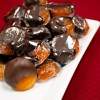 A pile of dark chocolate dipped apricots on a white tray with a red backdrop.