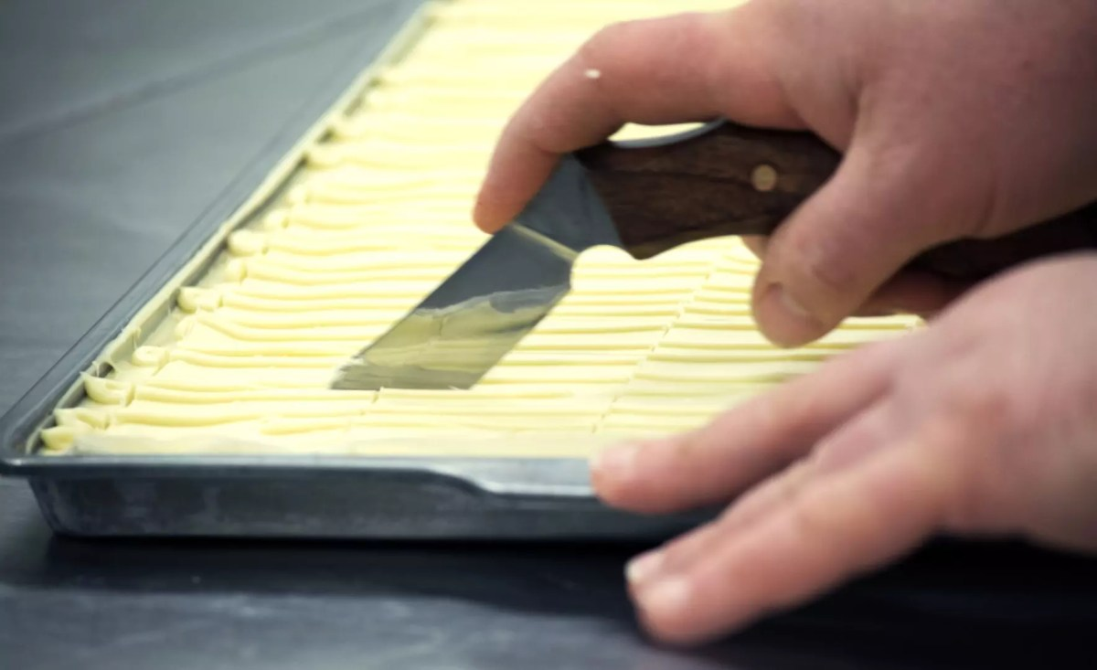 A hand holding an angled knife cutting a sheet of white chocolate pralines