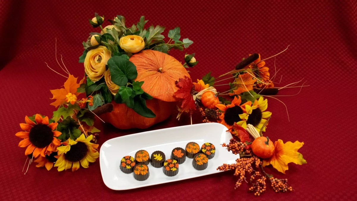 pumpkin and maple truffles laid out on a tray with a fall-themed background