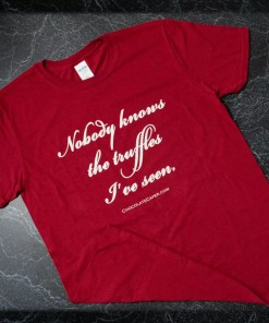 """A red t-shirt with the words """"Nobody knows the truffles I've seen"""" in white on the front."""