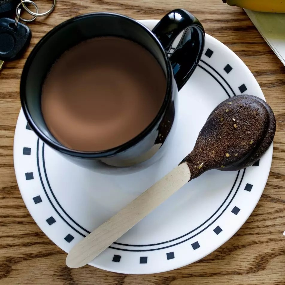 A chocolate dipped spoon on a plate.