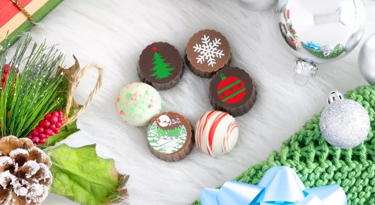 A group of 6 seasonally decorated truffles surrounded by holiday items.