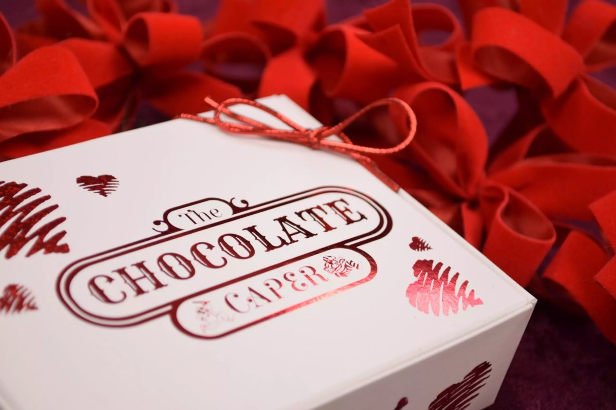 A red and white chocolate box with foil hearts on it on a bed of ribbon