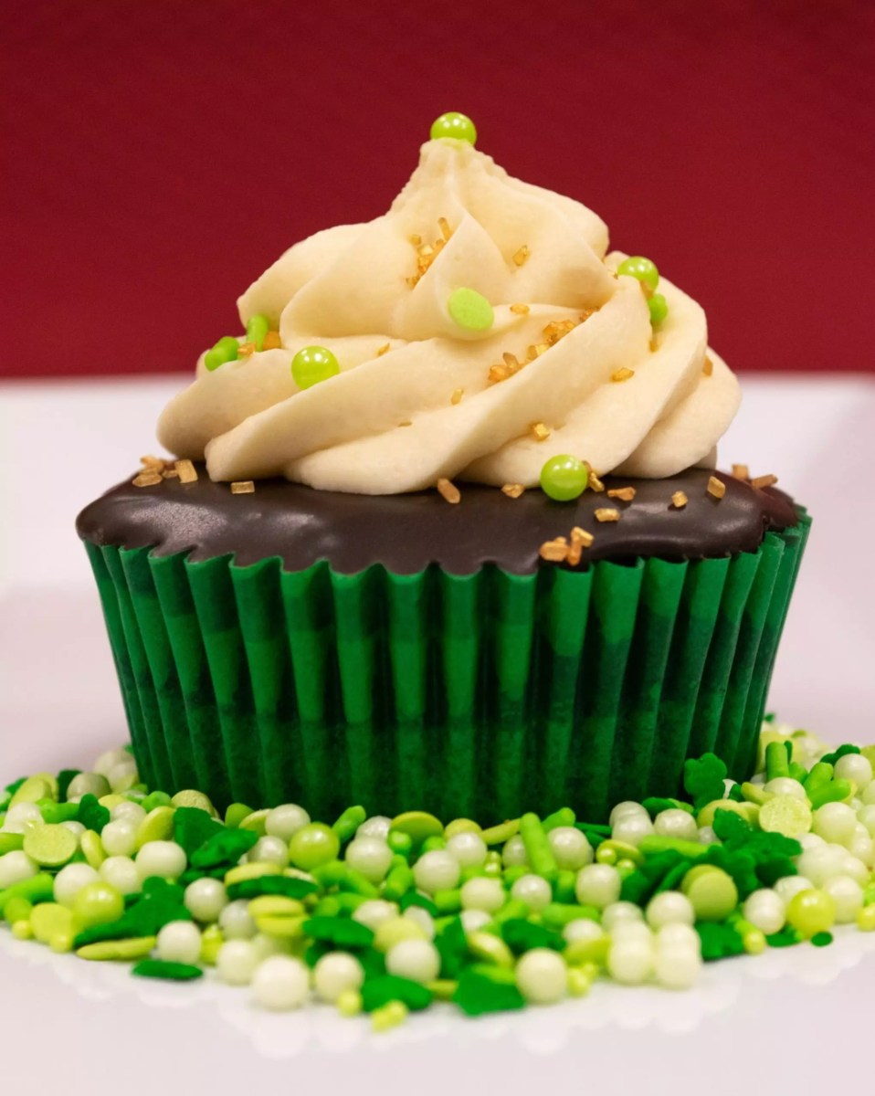 An irish cupcake from the front, with a cupcake topped with ganache and a spiral of buttercream icing, with green candy pearls surrounding it
