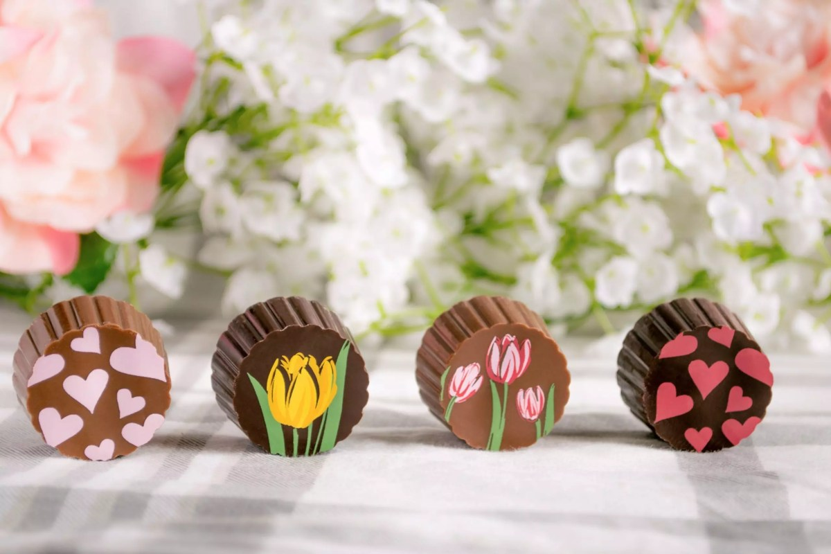 A row of four truffles - one each milk with pink hearts, dark with yellow tulips, milk with pink tulips, and dark with red hearts, all in front of a flower background