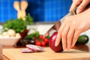 girl-slicing-onion-in-kitchen
