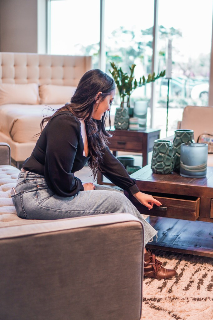 woman opening drawer to sustainable furniture coffee table