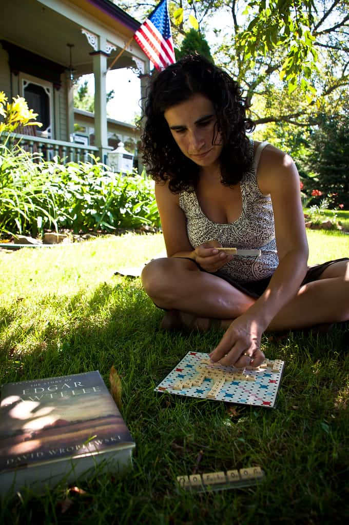A woman is enjoying sitting on a lawn and playing a board game. Lawns should be used and not merely maintained.