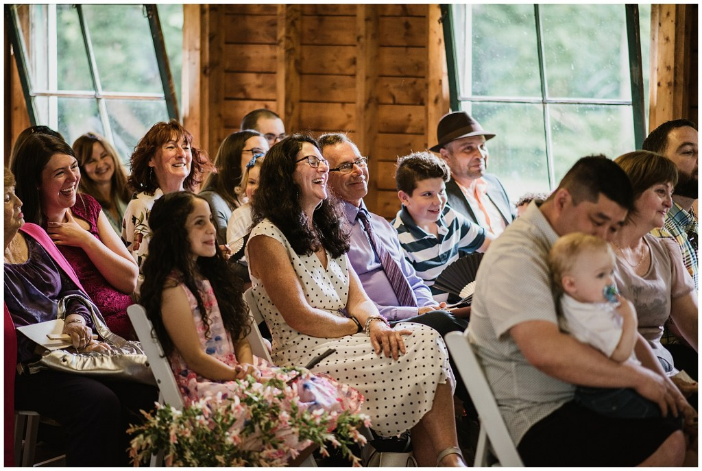 guests at wedding laugh during ceremony at crystal cliffs wedding venue