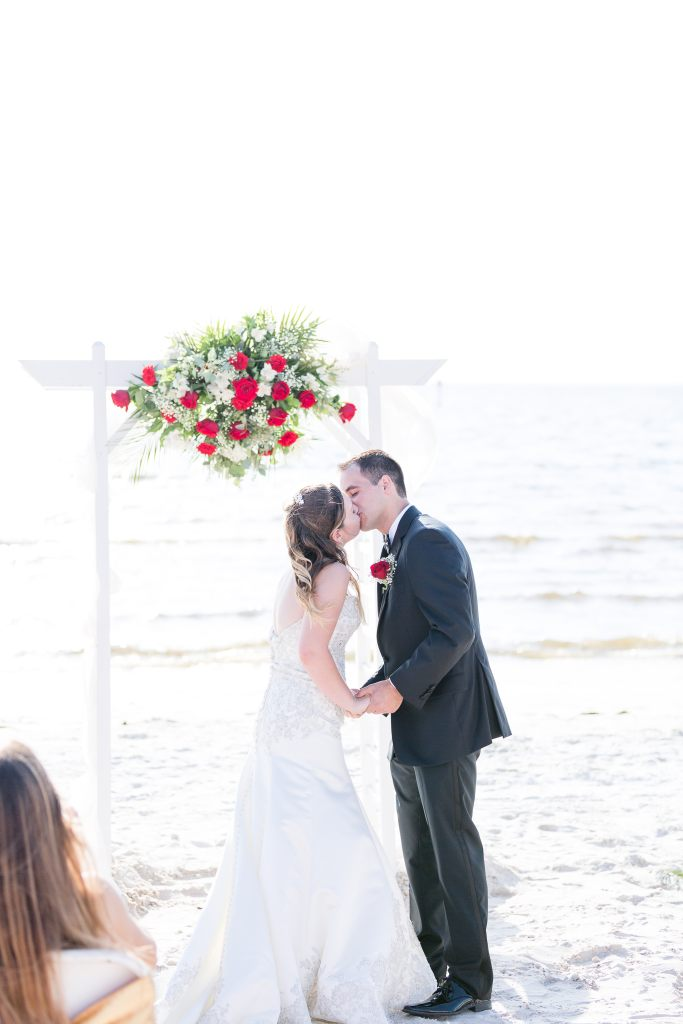 Bride and groom's first kiss during their outdoor beach wedding ceremony. Choosing the perfect wedding ceremony time for your wedding day   Chris Sosa Photography
