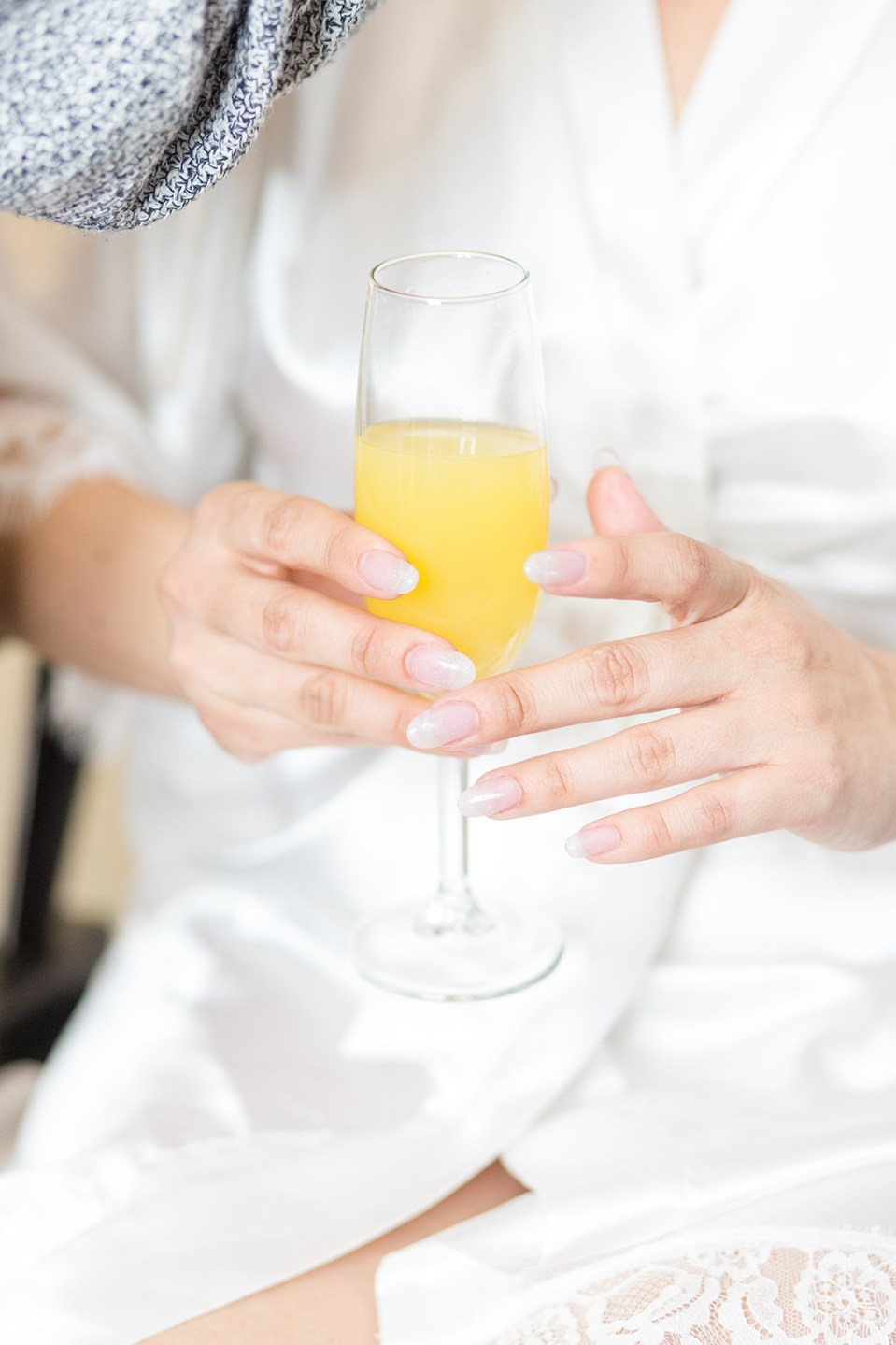 Bride is robe holding mimosa