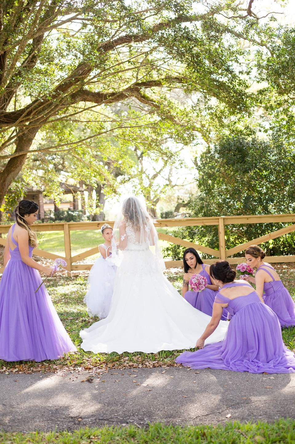 bridesmaids in purple dresses fluffing brides dress