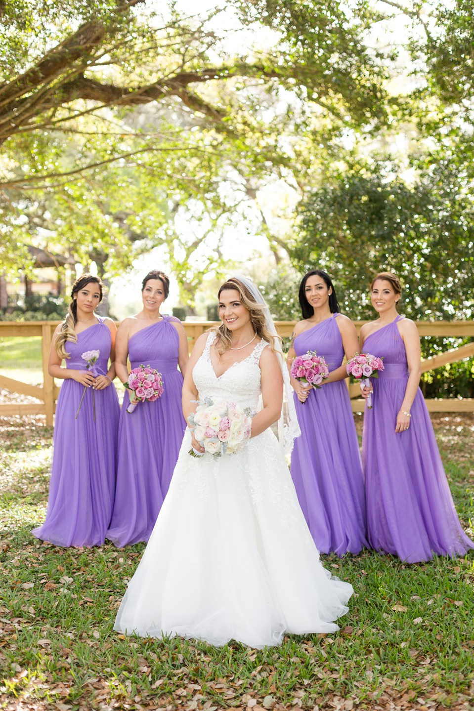 bride smiling with group of bridesmaids wearing purple dresses